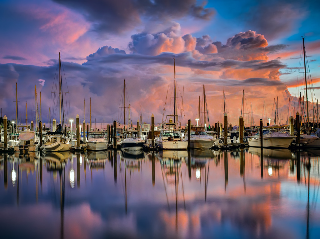 The subject here is the sailboats, so that's where the focus needs to be set. There is no point in worrying about anything else.